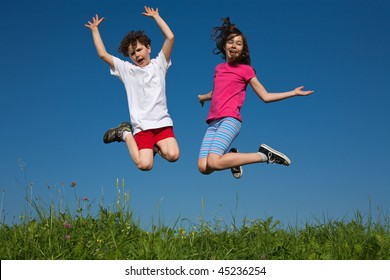 Kids jumping outdoor against blue sky