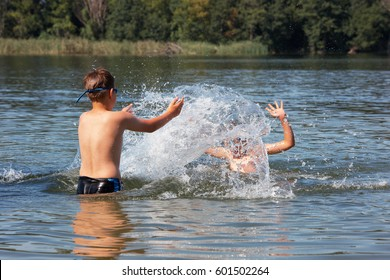 Kids jumping, swimming and playing with water in a polish lake, summer holiday in Greater Poland. Leisure - boys point of view. Beautiful childhood.