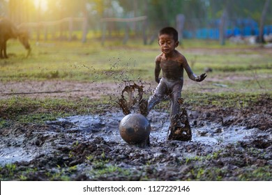 Kids kick the ball in the mud countryside thailand,