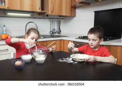 kids in the kitchen making dough mixing flour, milk, eggs in a glass bowl