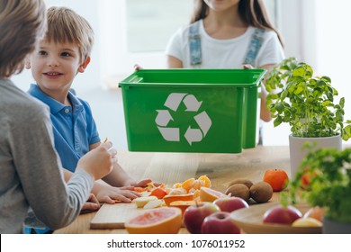 Kids in the kitchen throwing out fruit remains into a green bin for biodegradable waste