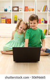 Kids with laptop, sitting on the floor playing