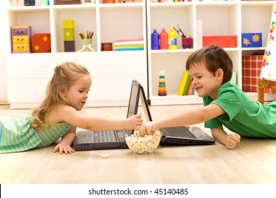 Kids with laptops eating popcorn in their room