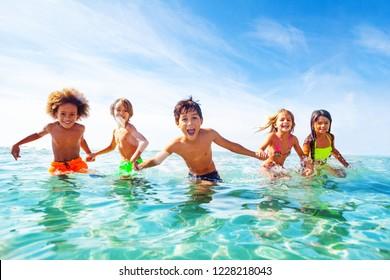 Kinder, die am Meer lachen und im Wasser spielen