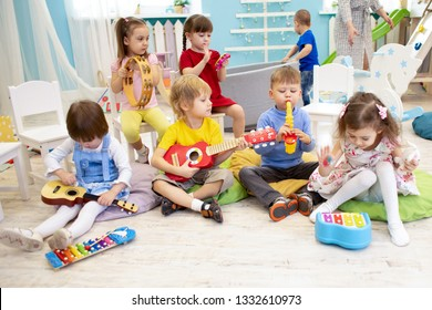 Kids learning musical instruments on lesson in kindergarten or preschool