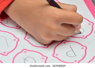 Kids learning to write letter by doing homework using pencil