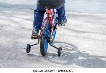 kid's legs peddling a child's first bike, with training wheels