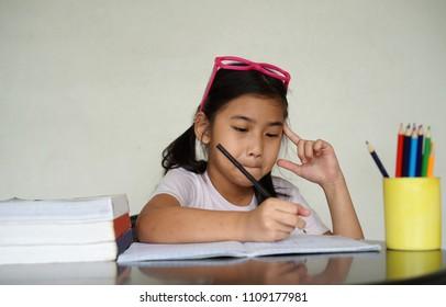 Kids little girl Asian wear glasses do homework write book