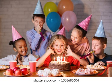 Kids looking at birthday cake with candles, having b-day party