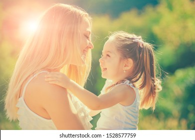 Kids love. Happy mother and daughter hugging over sun lights background. People happiness and love. Portrait close-up happy smiling mother with her little daughter on sunset background