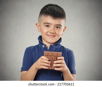 Kids love sweets. Portrait happy little boy eating whole bar of chocolate, isolated on grey wall background. Positive human emotions, face expressions. Food cravings