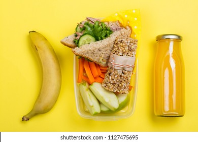 Kids lunch box with sandwich, vegetable sticks, granola bar, banana and juice on yellow background. Back to school concept