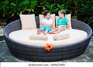 Kids at luxury resort relaxing at beach cabana