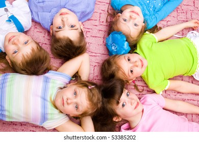 Kids lying on the floor and looking into camera