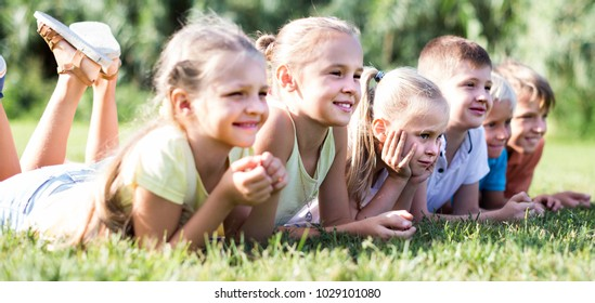 kids lying on green grass on bright summer day