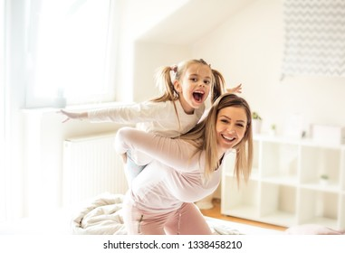 Kids make life the best kind of busy. Mother and daughter playing on bed.