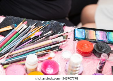 Kids makeup paints and paintbrushes on table during birthday party