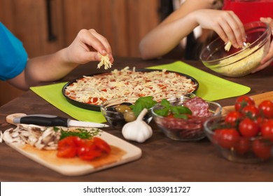Kids making a pizza at home - putting the grated cheese on, closeup on hands, shallow depth