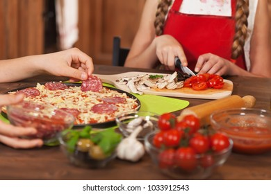 Kids making a pizza at home putting on the salami slices and preparing ingredients - closeup on hands