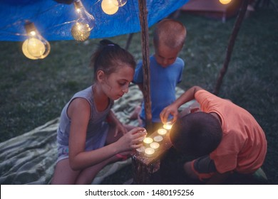 Kids making a small tent with candles and lampions in the backyard.