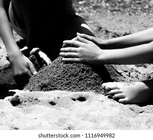 Kids making a tower of  sand at the beach