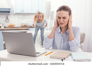 Kids manipulation. Working appealing mother covering ears while unruly girl screaming on background