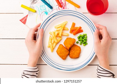 Kid's meal - chicken nuggets, french fries, carrot and green peas. Colorful dinner - plate in child's hands on white wooden table. Plate captured from above (top view, flat lay).