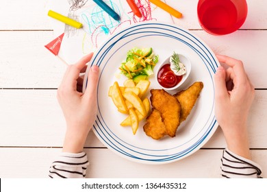 Kid's meal - fried chicken strips, french fries, salad and ketchup. Colorful dinner - plate in child's hands on white wooden table. Captured from above (top view, flat lay).