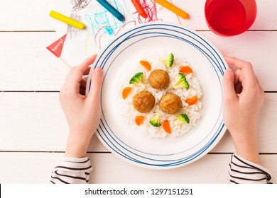 Kid's meal - meatballs, rice, broccoli and carrot. Colorful dinner - plate in child's hands on white wooden table. Plate captured from above (top view, flat lay).