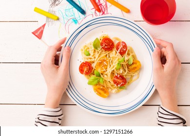 Kid's meal - spaghetti with cherry tomatoes and basil. Colorful dinner - plate in child's hands on white wooden table. Plate captured from above (top view, flat lay).
