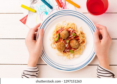 Kid's meal - spaghetti and meatballs. Colorful italian dinner - plate in child's hands on white wooden table. Plate captured from above (top view, flat lay).