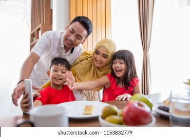 kids with mom and dad taking picture together while having breakfast