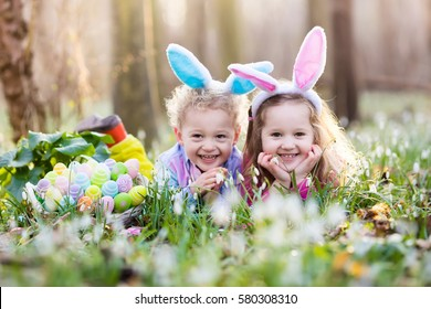 Kids on Easter egg hunt in blooming spring garden. Children with bunny ears searching for colorful eggs in snow drop flower meadow. Toddler boy and preschooler girl in rabbit costume play outdoors