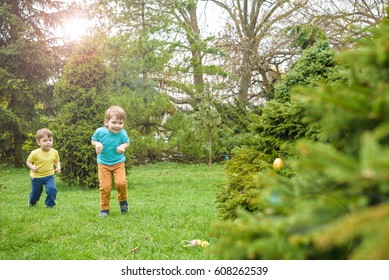 Kids on Easter egg hunt in blooming spring garden. Children searching for colorful eggs in flower meadow. Toddler boy and his brother friend kid boy play outdoors.