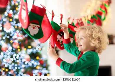 Kids opening Christmas presents. Child searching for candy and gifts in advent calendar on winter morning. Decorated Christmas tree for family with children. Little boy in Xmas pajamas.