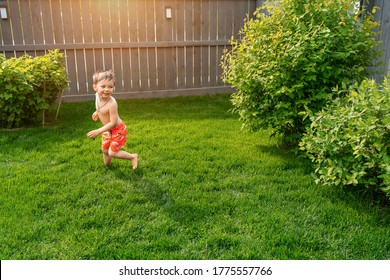 Kid's outdoor activity. Smile toddler boy wearing a orange swimming shorts running and playing with water splashes having fun in a backyard on a sunny hot summer day. Caucasian boy plays hide and seek
