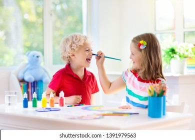 Kids paint. Child painting in white sunny study room. Little boy and girl drawing rainbow. School kid doing art homework. Arts and crafts for kids. Paint on children hands. Creative little artist.