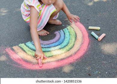 Kids paint outdoors. Portrait of a child girl drawing  a rainbow colored chalk on the asphalt on summer sunny day. Creative development of children - Shutterstock ID 1420851536