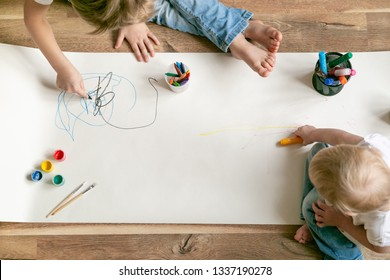 Kids painting with different materials on large canva on the flour, top view,