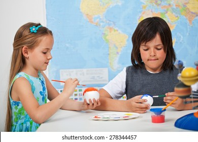 Kids painting the planets in art and science class - for a solar system scale model- focus on the girl face