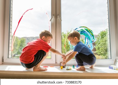 Kids painting a rainbow on the window