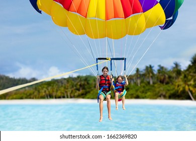 Kids parasailing. Water sport on summer vacation. Brother and sister flying in tropical ocean resort. Sea and beach fun. Rainbow parachute. Teenage boy and little girl fly.
