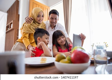 kids and parent using tablet pc at dining room together