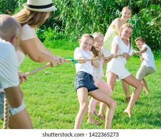 Kids with parents playing tug of war during joint outdoors games on sunny day