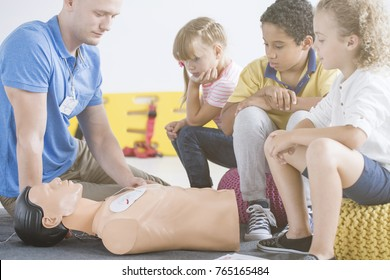 Kids paying attention during demonstrative lesson with medical equipment during course with male paramedic