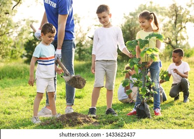 Kids planting tree with volunteer in park