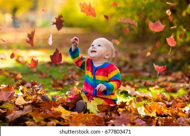 Kids play in autumn park. Children throwing yellow and red leaves.Baby with oak and maple leaf. Fall foliage. Family outdoor fun in autumn. Toddler kid or preschooler child in fall.