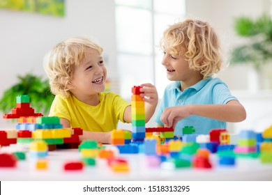 Kids play with colorful blocks. Little boy building tower at home or day care. Educational toy for young child. Construction creative game for baby or toddler kid. Mess in kindergarten playroom.
