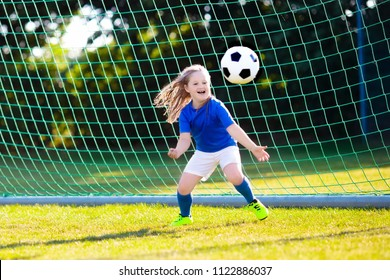 Kids play football on outdoor field. Children score a goal at soccer game. Little girl kicking ball. Running child in team jersey and cleats. School football club. Sports training for young player.