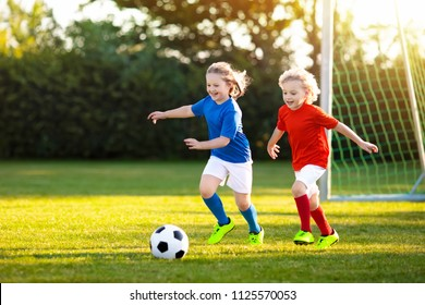 Kids play football on outdoor field. Children score a goal at soccer game. Girl and boy kicking ball. Running child in team jersey and cleats. School football club. Sports training for young player.